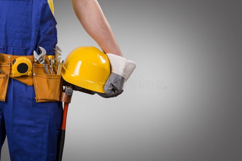 Trabalhador da construção que guarda o capacete no fundo cinzento imagens de stock royalty free