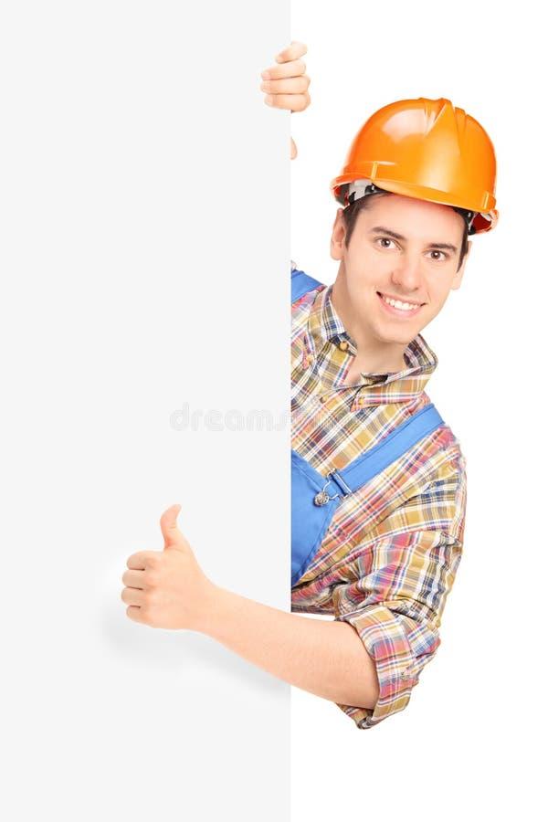 Trabalhador da construção que levanta e que dá o polegar acima em um painel foto de stock royalty free