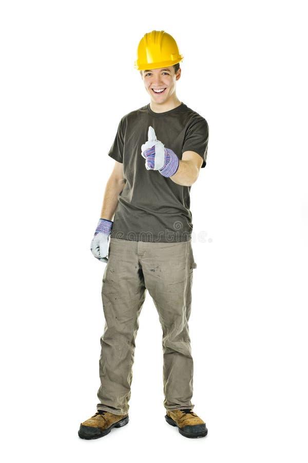 Trabalhador da construção que mostra os polegares acima imagem de stock
