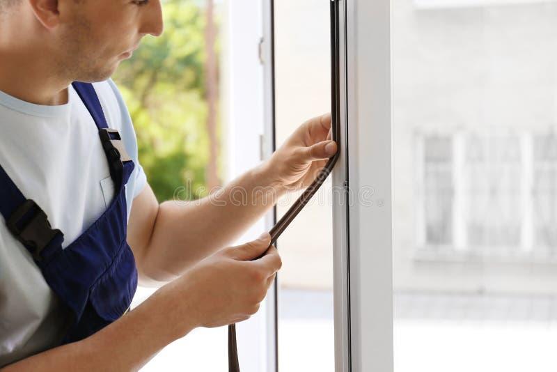 Trabalhador da construção que põe a fita da espuma da selagem sobre a janela foto de stock