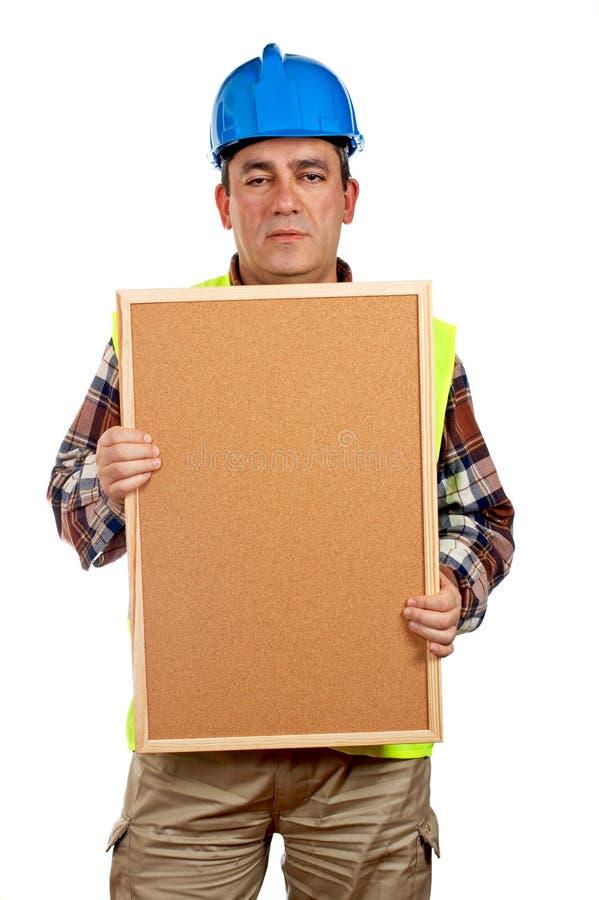 Trabalhador da construção que prende o corkboard vazio fotografia de stock