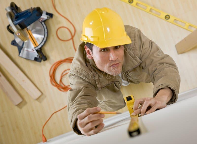 Trabalhador da construção que usa a fita de medição imagens de stock royalty free