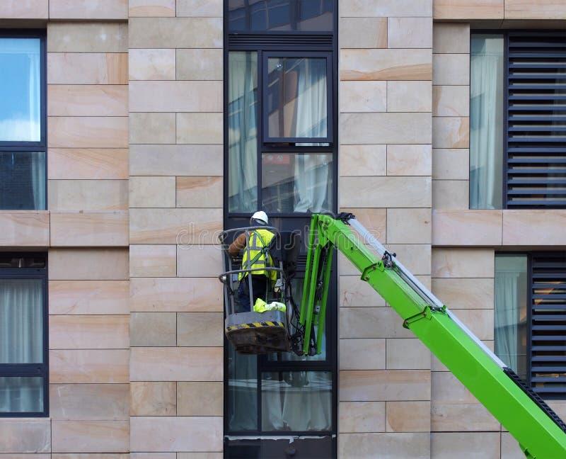 Trabalhador da construção Unidentifiable em uma plataforma de trabalho aéreo verde em um grande canteiro de obras urbano de abrig fotos de stock royalty free