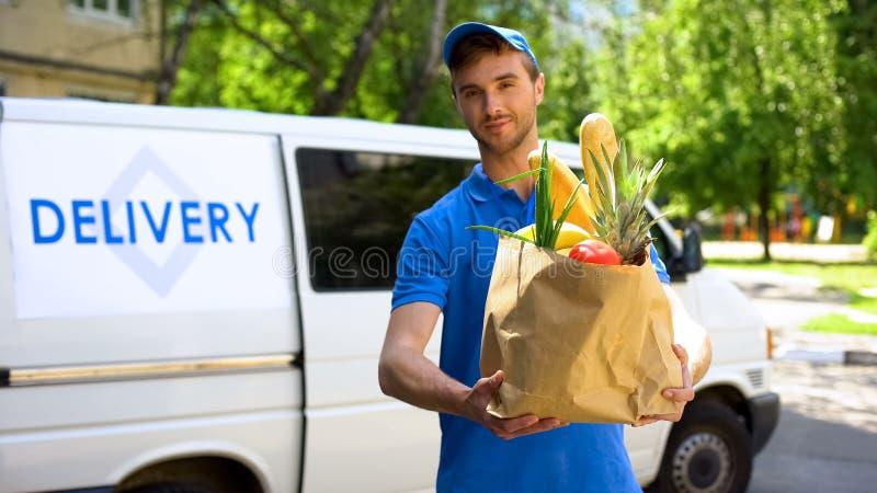 Trabalhador da empresa de entrega que guarda o saco de mantimento, ordem do alimento, serviço do supermercado foto de stock royalty free