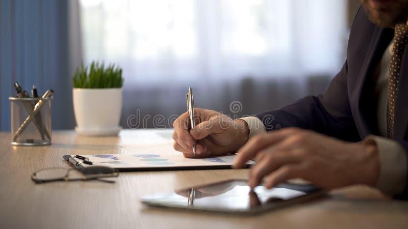 Trabalhador da empresa que verifica a informação na tabuleta para marcar gráficos, relatório estatístico imagem de stock