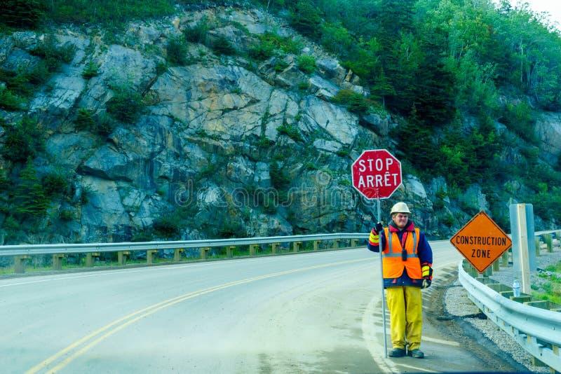 Trabalhador da estrada que guarda um sinal bilíngue da parada fotografia de stock royalty free