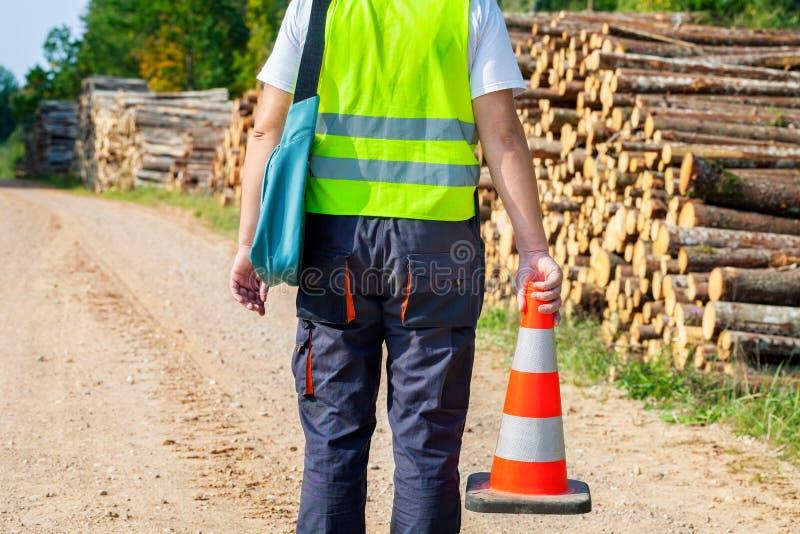 Trabalhador da floresta com o cone da estrada na pilha próxima do log da estrada rural fotos de stock royalty free