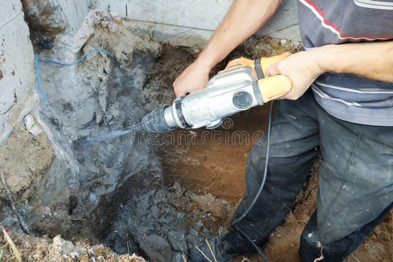 Trabalhador da indústria da construção civil que usa a broca de martelo pneumático para cortar acima o tijolo concreto da parede, fotos de stock royalty free