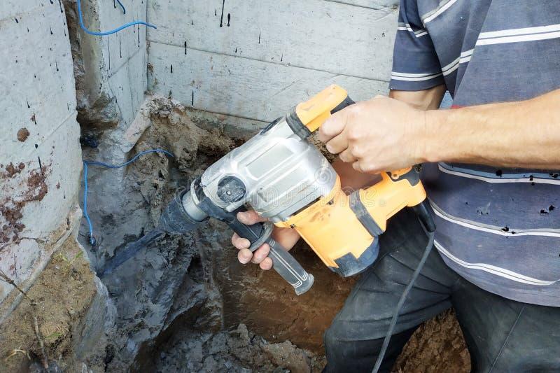 Trabalhador da indústria da construção civil que usa a broca de martelo pneumático para cortar acima o tijolo concreto da parede, fotografia de stock royalty free