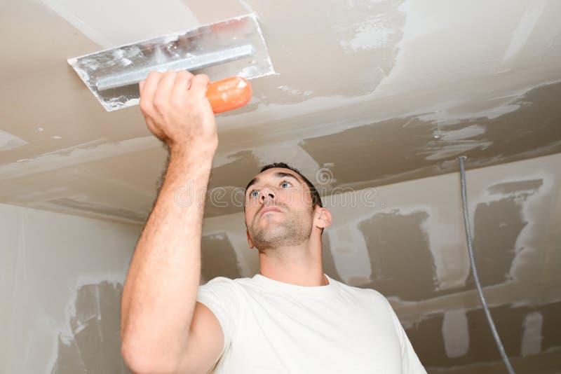 Trabalhador da indústria da construção civil com ferramentas que emplastra paredes e que renova a casa no canteiro de obras fotos de stock