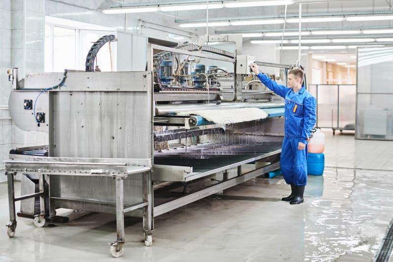 Trabalhador da lavanderia em processo do trabalho na máquina automática para lavar dos tapetes foto de stock royalty free