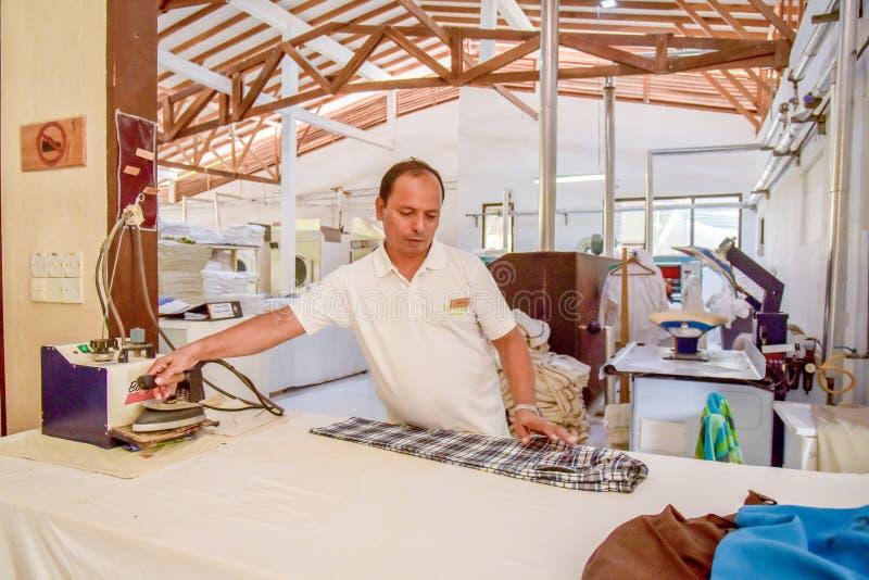Trabalhador da lavanderia no uniforme com ferro fotos de stock royalty free
