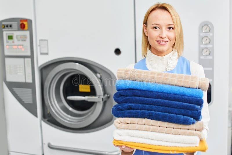 Trabalhador da menina que guarda toalhas limpas de serviço de lavanderia fotografia de stock