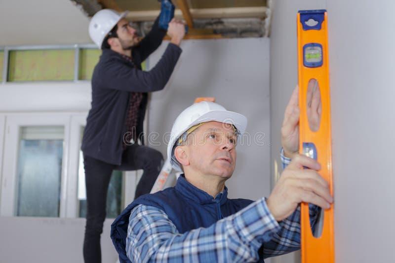 Trabalhador da renovação da construção que usa o nível de espírito imagens de stock royalty free