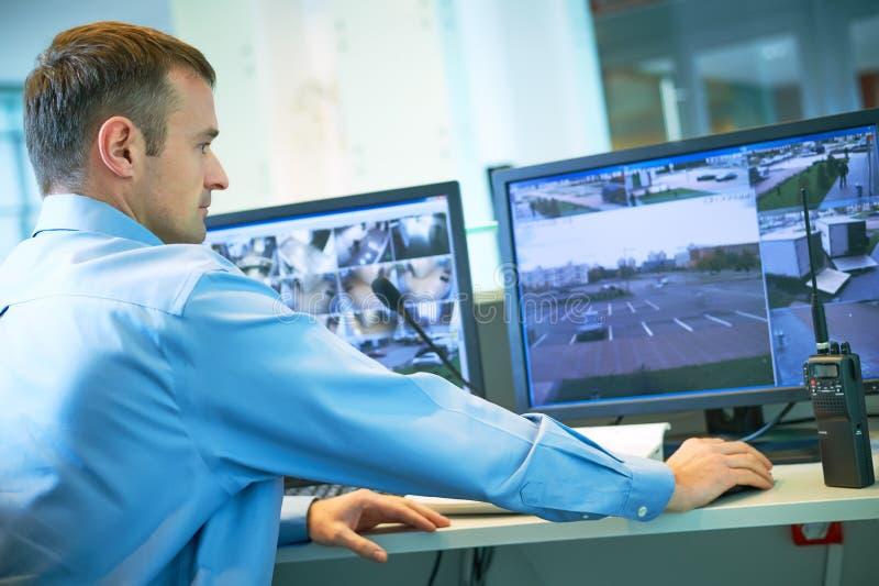 Trabalhador da segurança durante a monitoração Sistema de vigilância video imagem de stock royalty free