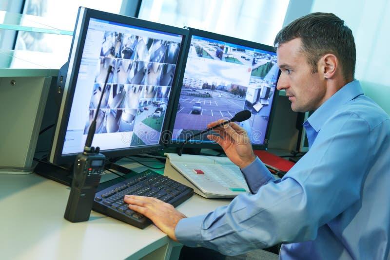 Trabalhador da segurança durante a monitoração Sistema de vigilância video imagem de stock