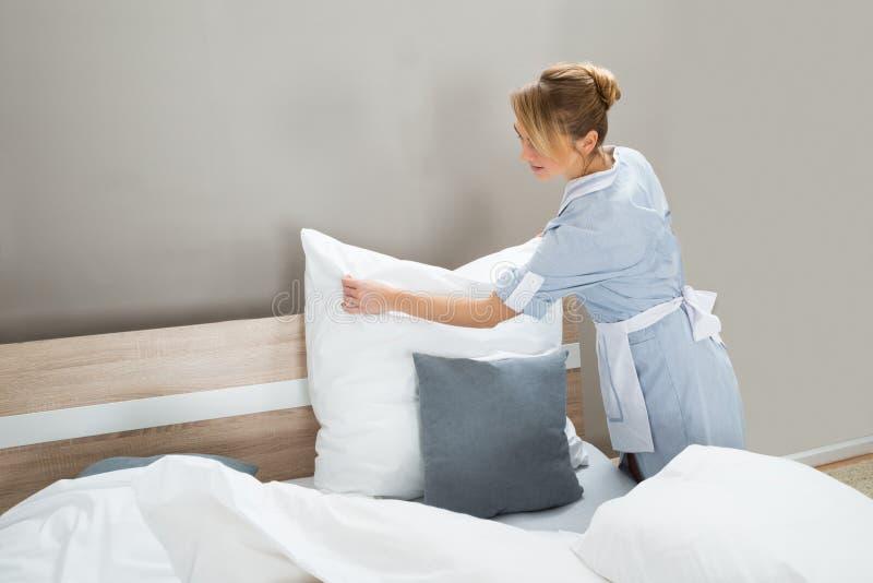 Trabalhador das tarefas domésticas que põe os descansos brancos imagem de stock royalty free