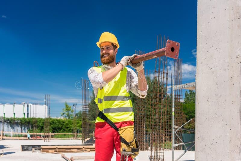 Trabalhador de colarinho azul que leva uma barra metálica pesada durante o trabalho fotografia de stock royalty free