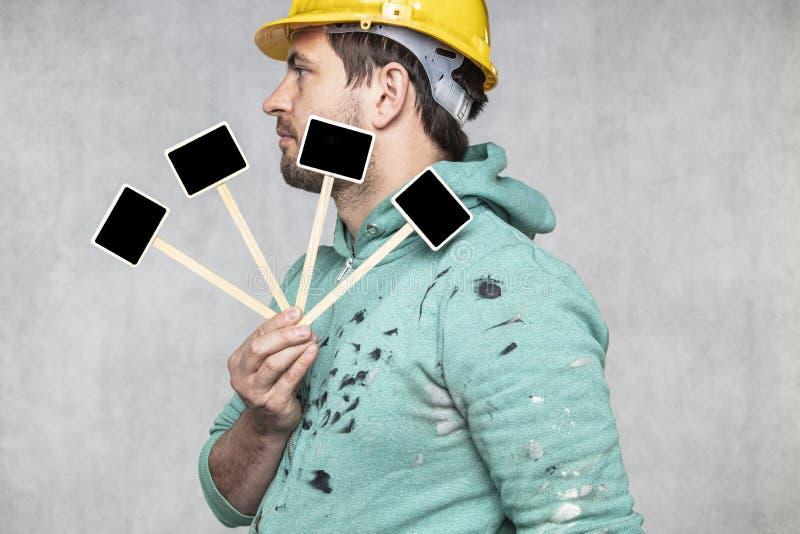 Trabalhador de construção segurando um quadro-negro com espaço para texto ou texto, espaço de cópia, visão lateral imagens de stock