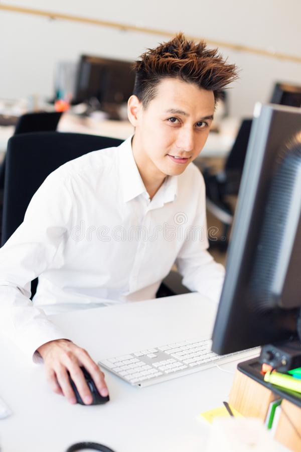 Trabalhador de escritório asiático novo em sua mesa fotos de stock