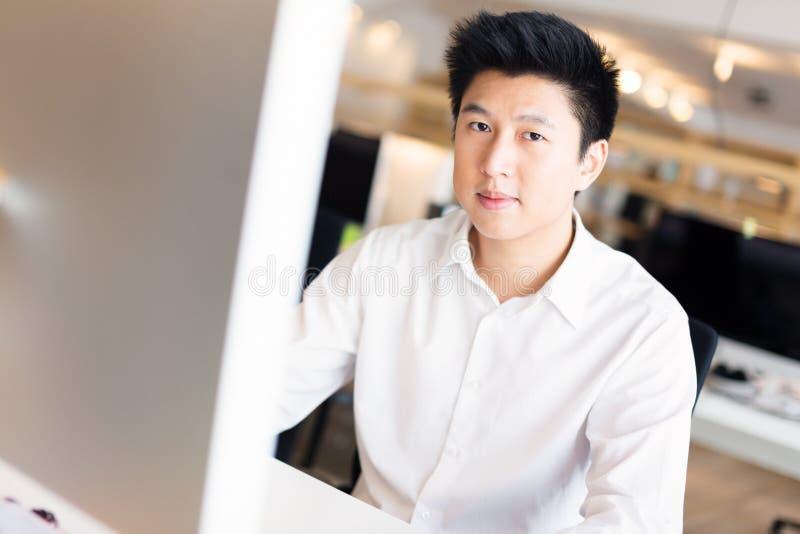 Trabalhador de escritório asiático novo em sua mesa fotografia de stock royalty free