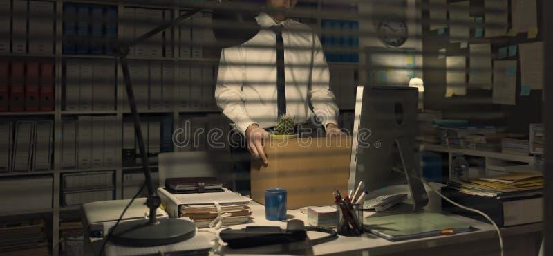 Trabalhador de escritório ateado fogo que guarda uma caixa fotos de stock