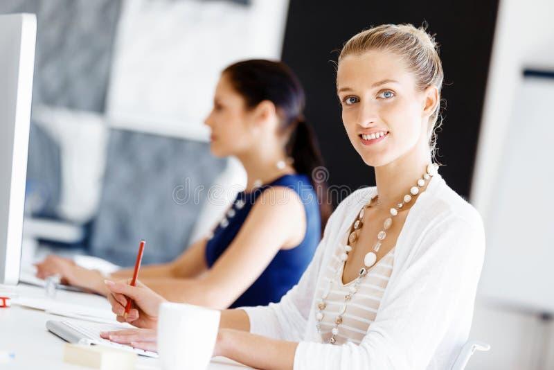 Trabalhador de escritório atrativo que senta-se na mesa foto de stock