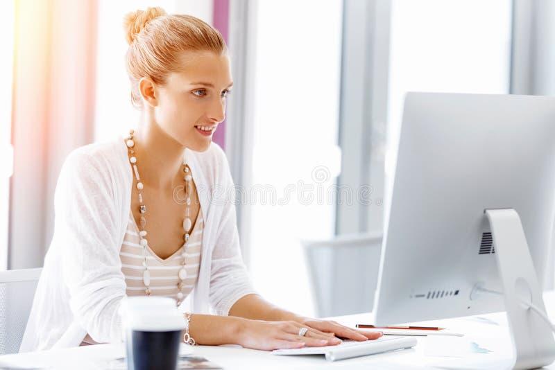 Trabalhador de escritório atrativo que senta-se na mesa imagem de stock