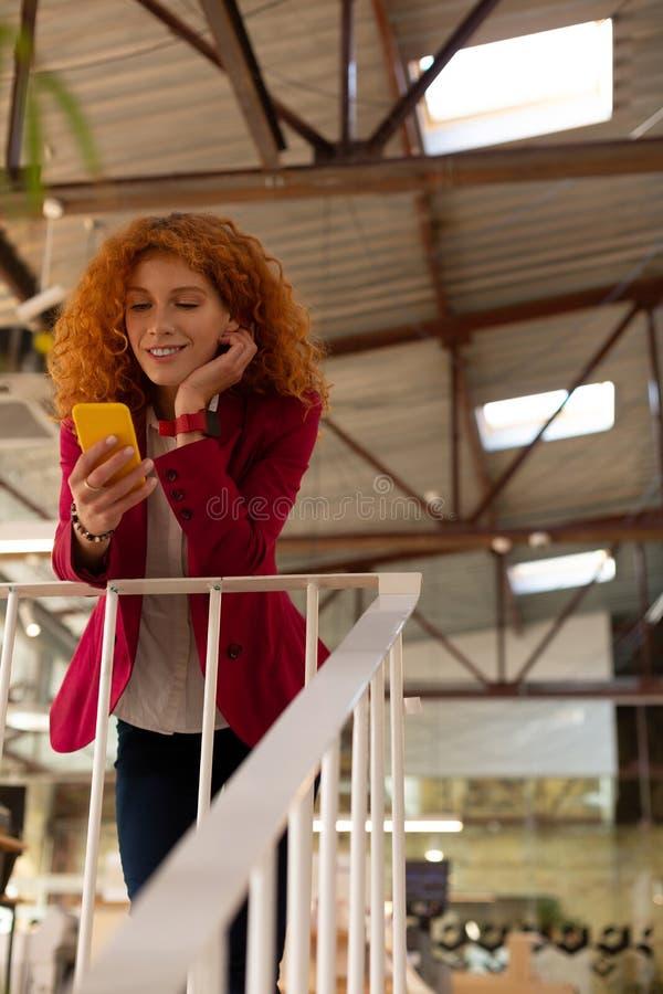 Trabalhador de escritório de cabelos vermelhos usando o telefone desfrutando uma pequena pausa foto de stock royalty free
