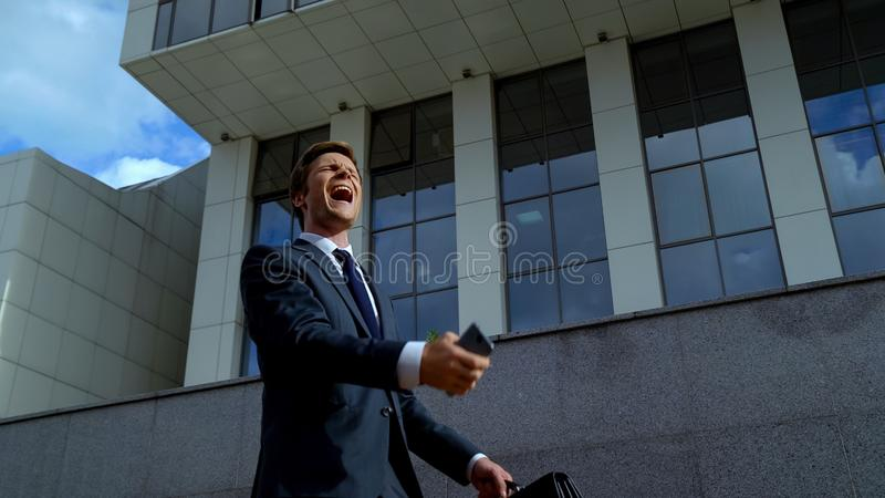 Trabalhador de escritório extremamente feliz que comemora a promoção, boa notícia do telefone imagem de stock royalty free