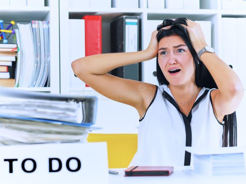 Trabalhador de escritório fêmea novo chocado pela enorme quantidade do documento Conceitos do fim do prazo imagens de stock