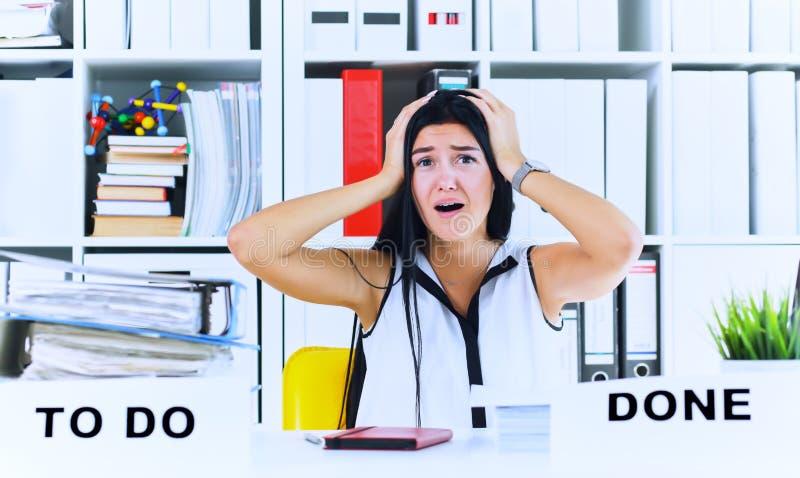 Trabalhador de escritório fêmea novo chocado pela enorme quantidade do documento Conceitos do fim do prazo fotografia de stock royalty free