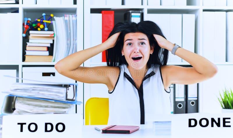 Trabalhador de escritório fêmea novo chocado pela enorme quantidade do documento Conceitos do fim do prazo imagens de stock royalty free