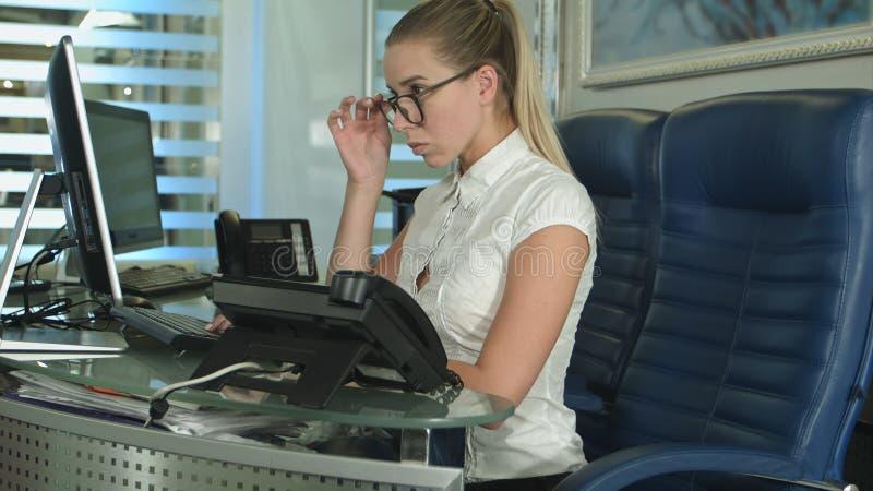 Trabalhador de escritório fêmea ocupado que usa o computador fotografia de stock