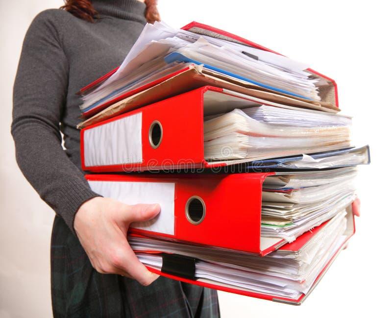 Trabalhador de escritório fêmea que leva uma pilha de arquivos foto de stock royalty free