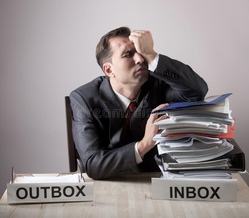 Trabalhador de escritório forçado com uma pilha de papel imagens de stock