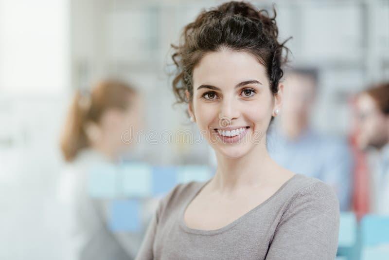 Trabalhador de escritório novo que sorri e que levanta foto de stock royalty free