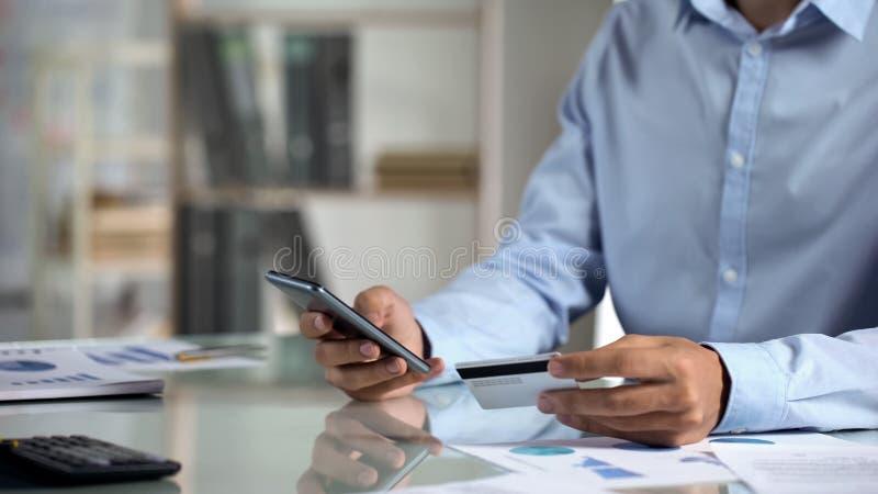 Trabalhador de escritório que compra em linha, dados de datilografia do cartão de crédito na aplicação do smartphone imagem de stock