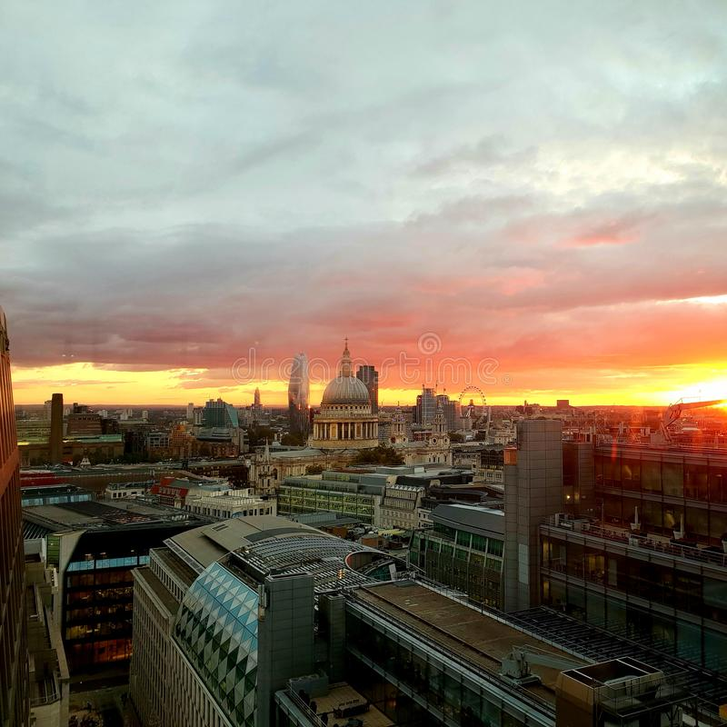 Trabalhador de escritório que toma imagens no móbil do nascer do sol impressionante sobre a vista da catedral de St Paul fotografia de stock