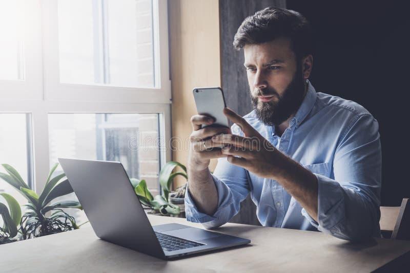 Trabalhador de escritório relaxando, jogando on-line no smartphone Homem a transferir aplicações no seu dispositivo móvel Macho v fotos de stock royalty free