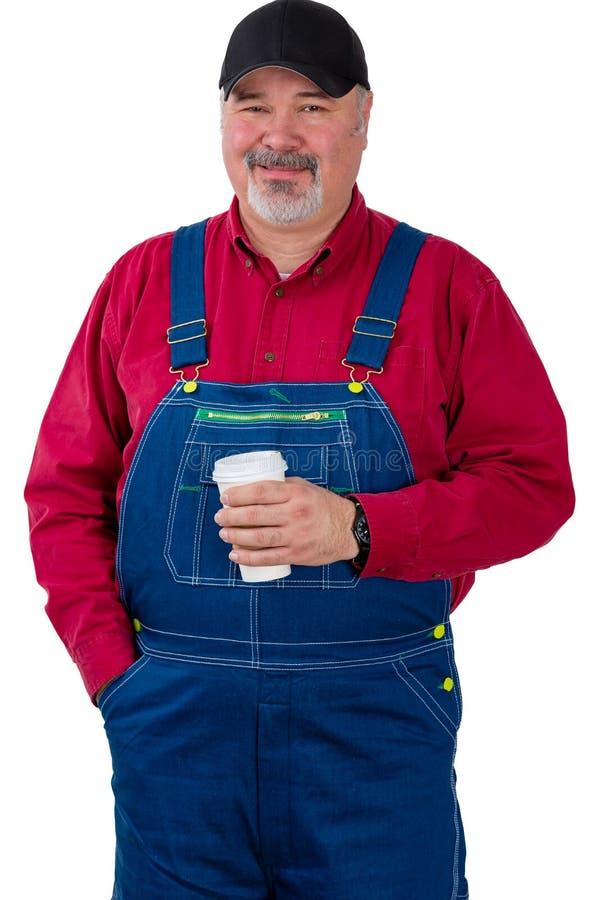 Trabalhador de exploração agrícola de sorriso amigável que guarda o café fotos de stock