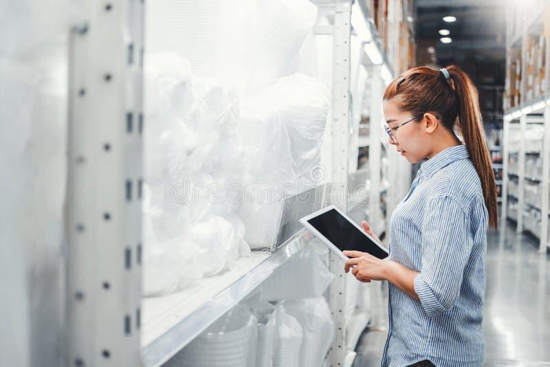 Trabalhador de mulher asiático que trabalha com as caixas de verificação digitais pacotes logísticos das fontes da importação da  imagem de stock royalty free