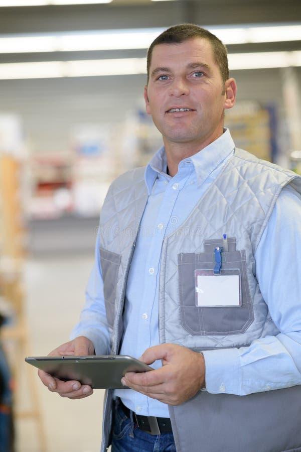 Trabalhador de sorriso com a tabuleta no armazém fotografia de stock royalty free