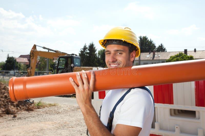 Trabalhador de sorriso com uma tubulação de água imagem de stock