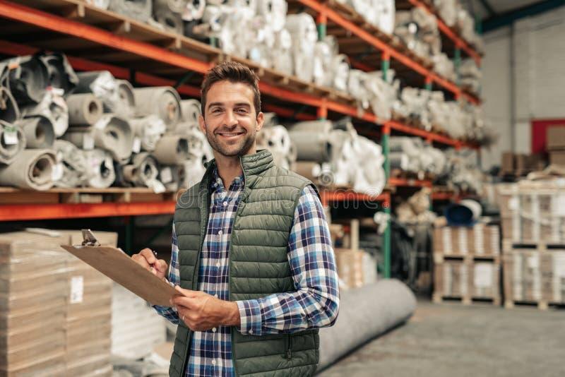 Trabalhador de sorriso que faz o inventário em um assoalho do armazém fotografia de stock royalty free