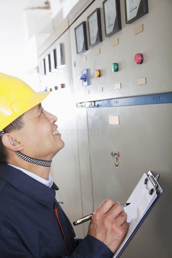 Trabalhador de sorriso que guarda a prancheta e a verificação de controles em uma planta de gás, Pequim, China foto de stock royalty free
