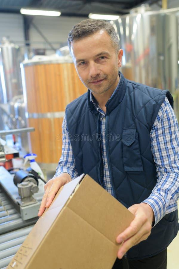 Trabalhador de sorriso que olha a câmera no armazém fotografia de stock