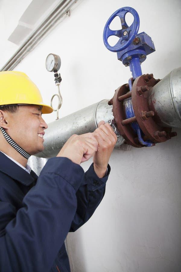 Trabalhador de sorriso que verifica o equipamento do oleoduto em uma planta de gás, Pequim, China foto de stock royalty free