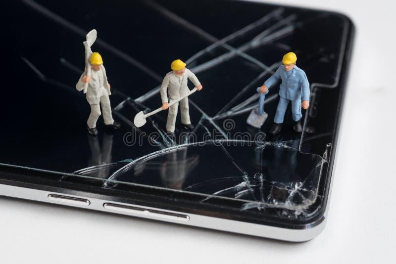 Trabalhador diminuto que trabalha em tela rachada do smartphone imagem de stock