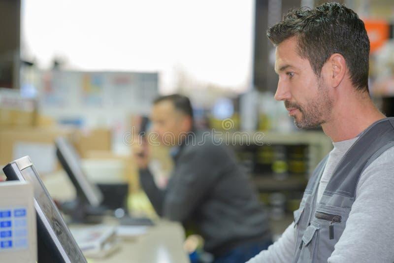 Trabalhador do armazém do retrato que verifica o computador fotografia de stock